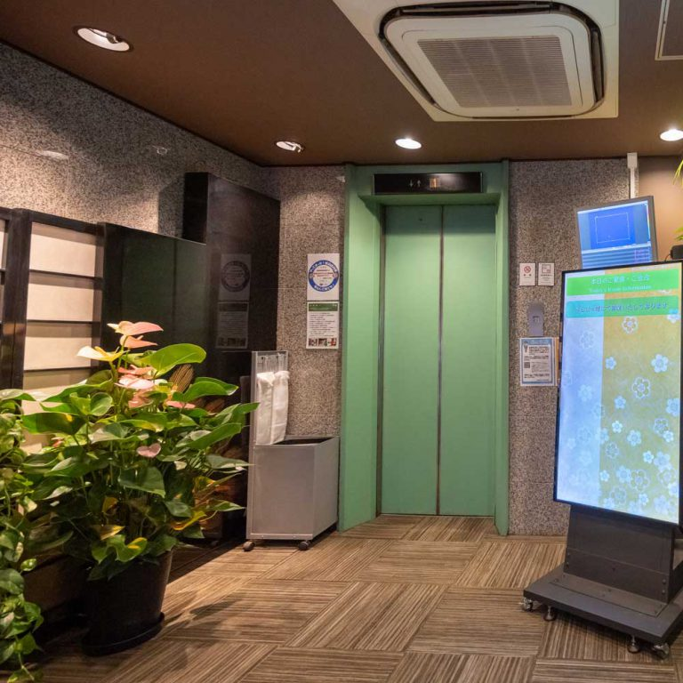1階エントランス - エレベータ前に宴会ご案内パネルを設置しております